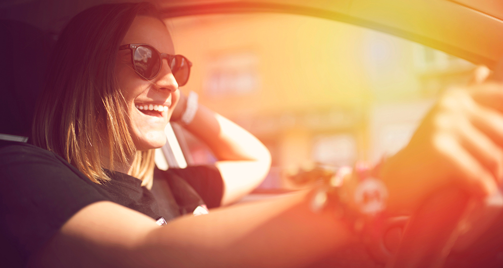 How to safely buy a used car_Young woman enjoying driving her car