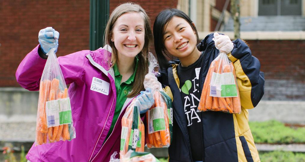 Portland State University volunteers holding up carrots_Oregon Food Bank Refer a Friend