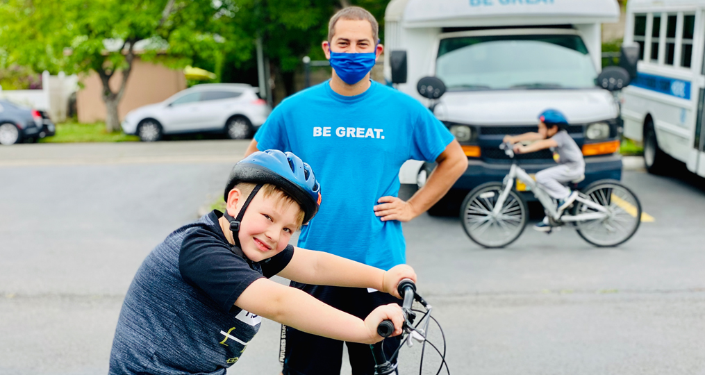Refer a Friend and Help the Boys & Girls Club in Your Community_volunteer and boy on bike