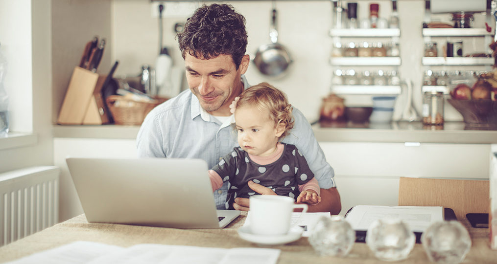 Strategies for Quitting the Paycheck-To-Paycheck Life_Father and child sitting at the kitchen table looking at laptop