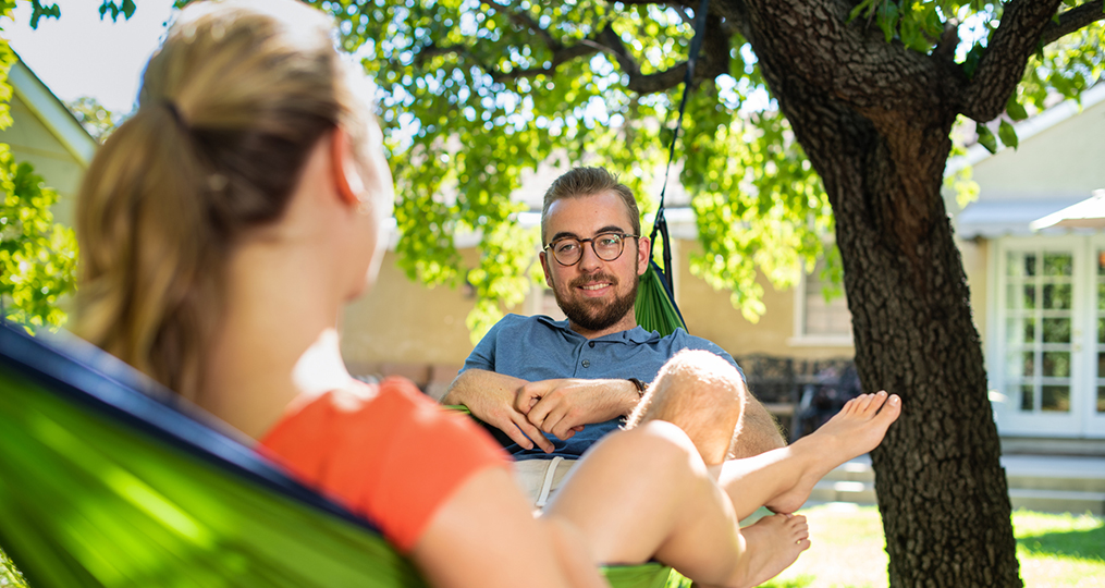 Take the time to organize your finances_Young man and woman sitting in a hammock having a discussion