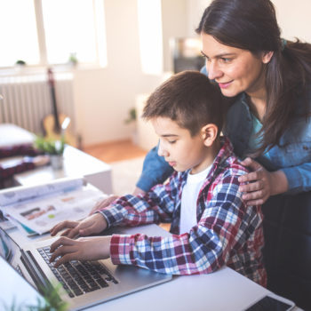 The Biggest Cybersecurity Questions for Parents_Mom encouraging son to use laptop