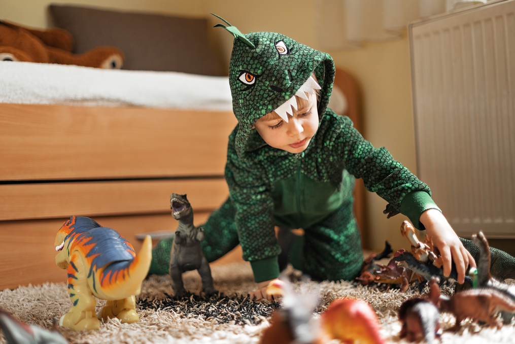 CUNA Youth Savings Month 2021_young boy in dinosaur costume playing with toys in his bedroom