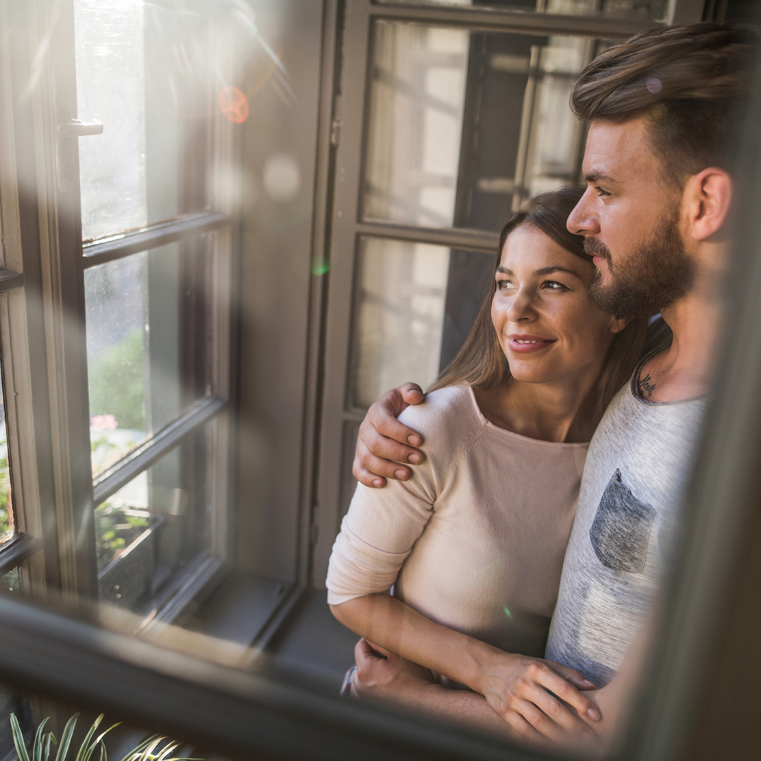 couple standing at the window of their new home looking out into their front lawn