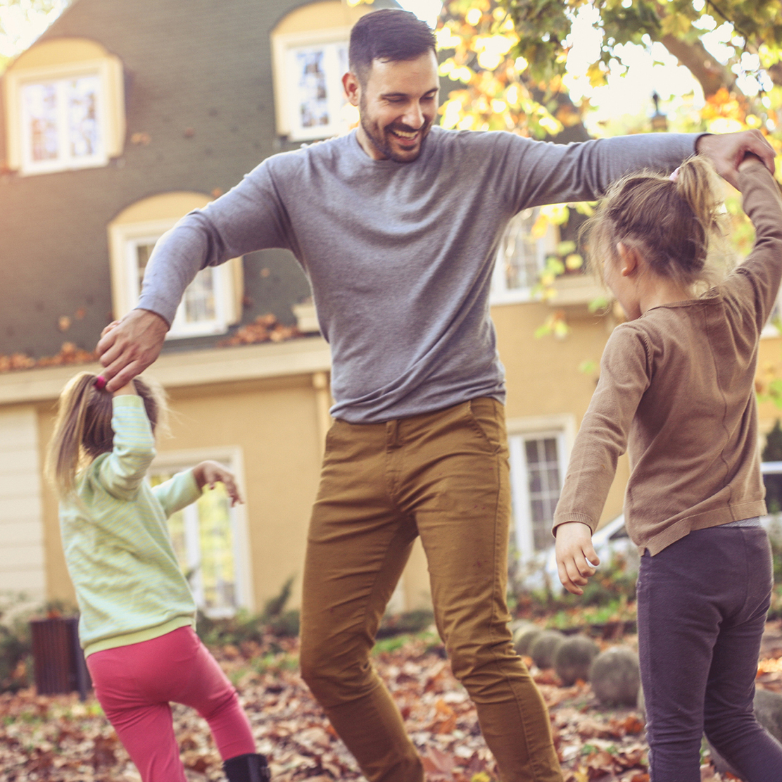 father dancing and playing with his two daughters in their yard among the fall leaves