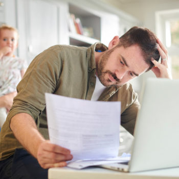 managing personal finances during a crisis_Man sitting at kitchen table reviewing bills