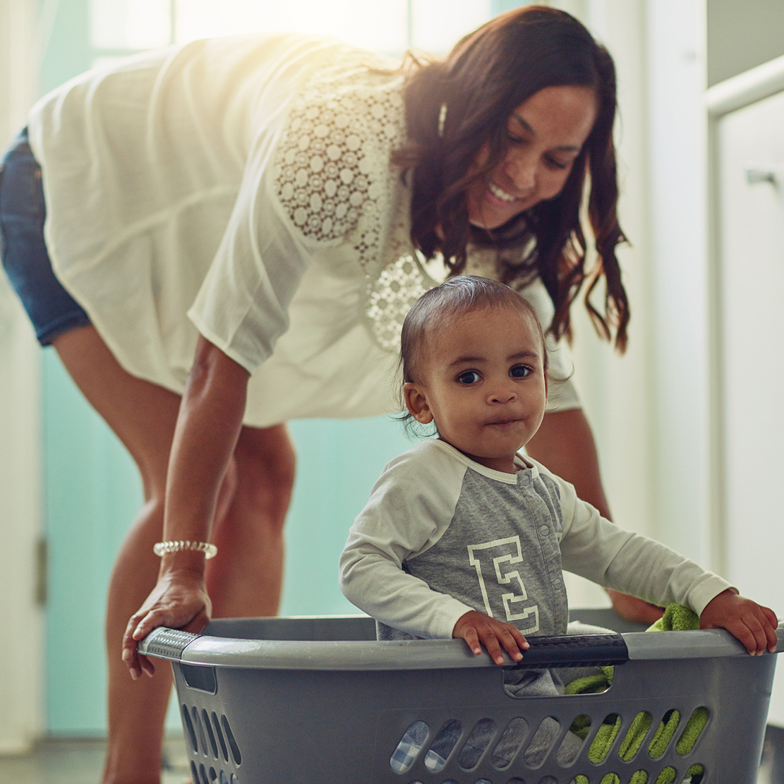 mother pushing around her baby in a laundry basket