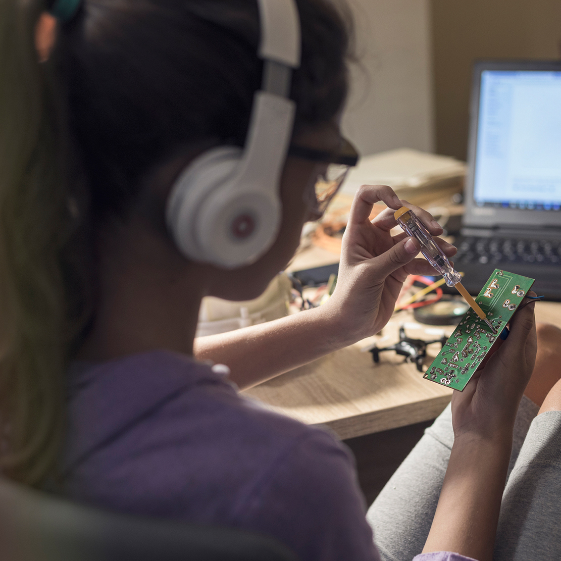 teenage girl working on a circuit board while listening to music