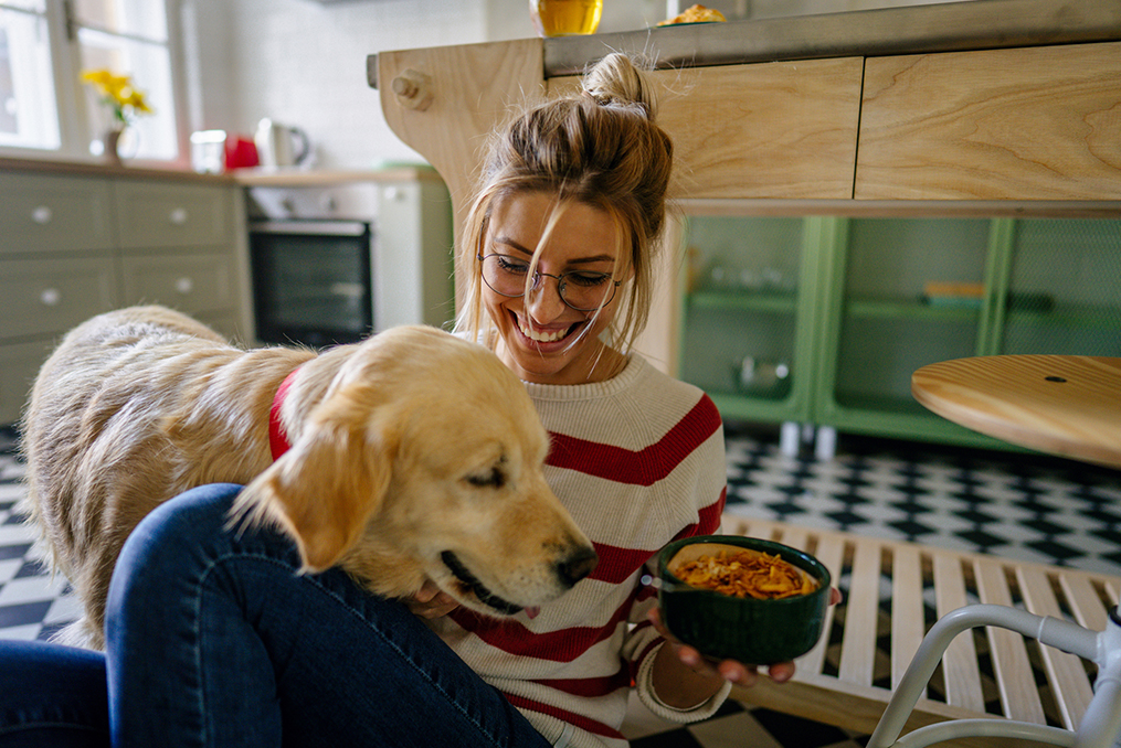 what young adults need to know about generational changes in spending habits_young woman laughing while holding a bowl of food