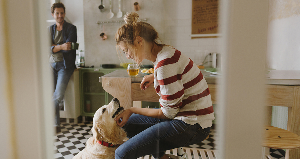 what young adults need to know about generational changes in spending habits_young woman smiling while petting her dog