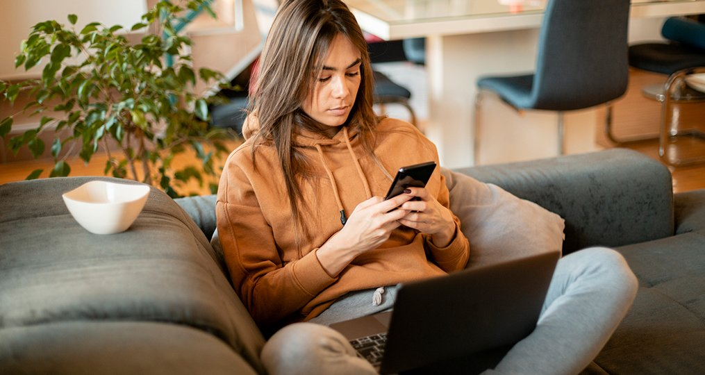 why malware is dangerous and how to protect yourself_woman sitting on coach reviewing looking up malware solutions on her mobile phone