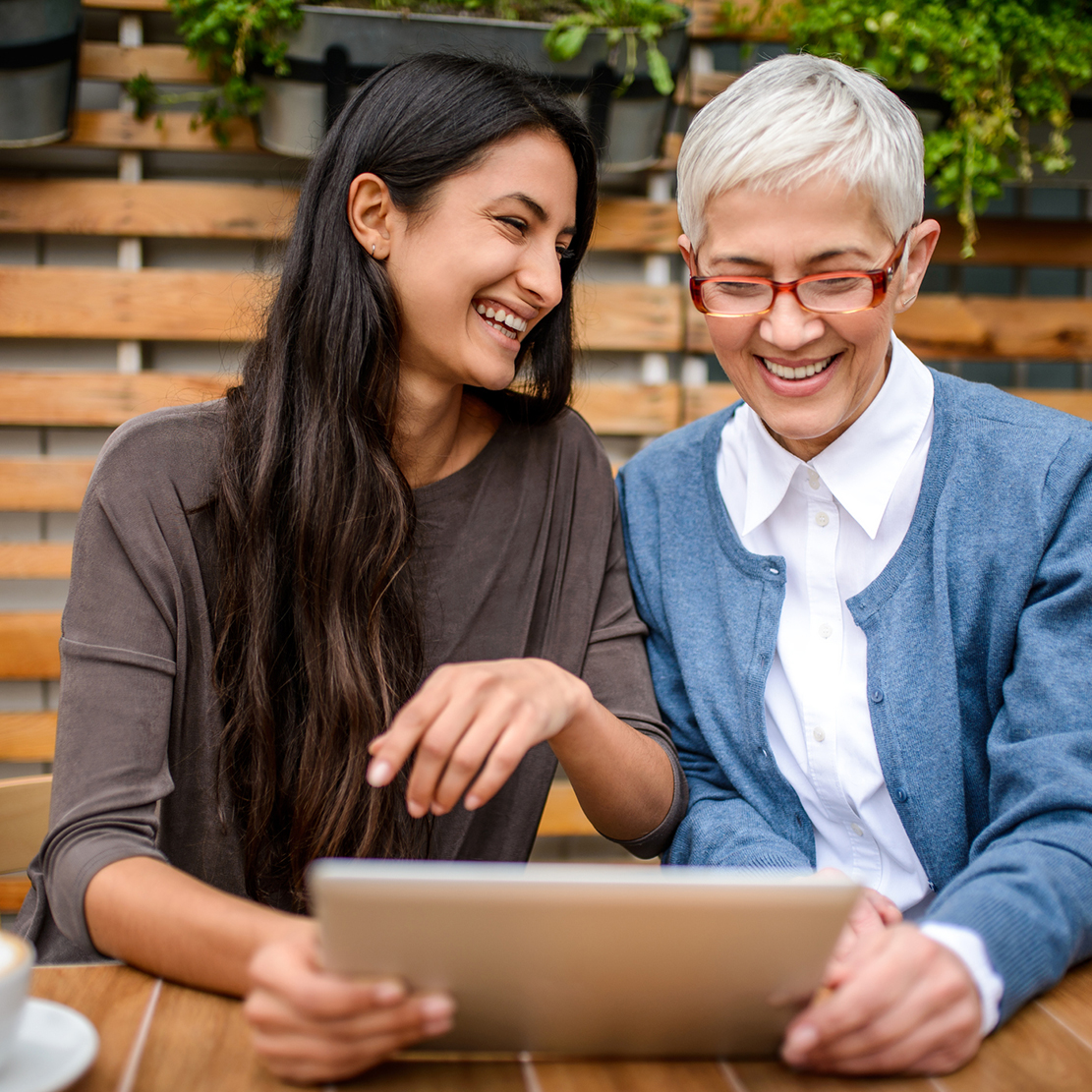 woman and her grandma looking at a tablet together sitting on the patio