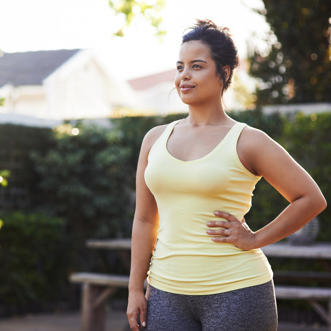 woman in workout clothes standing in her back yard