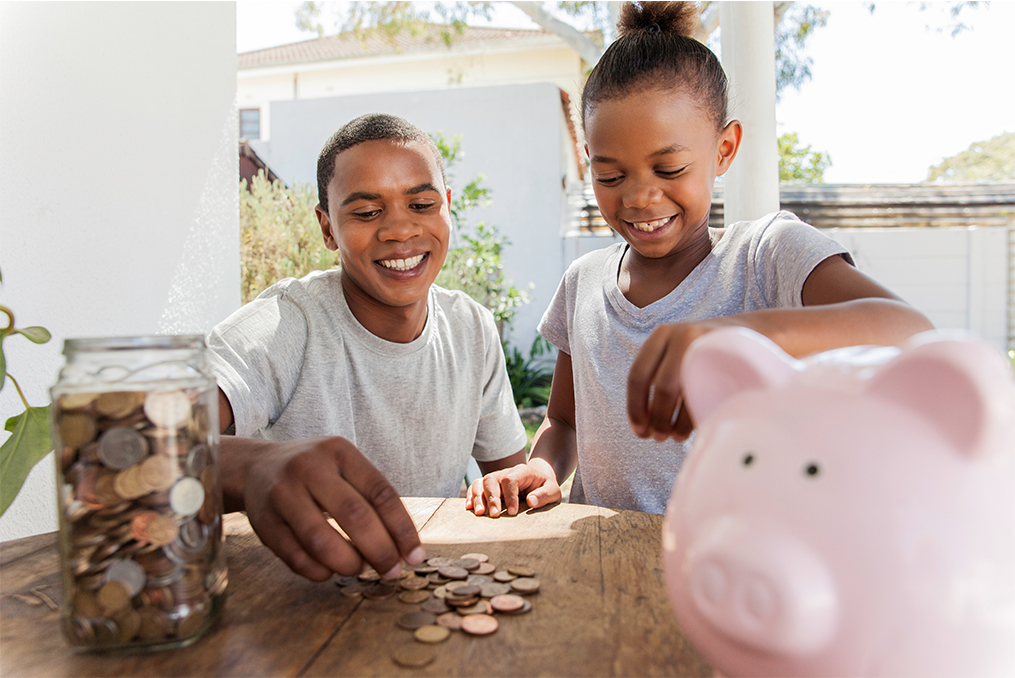 OnPoint Savers Account_two siblings counting coins from their change jar and piggy bank