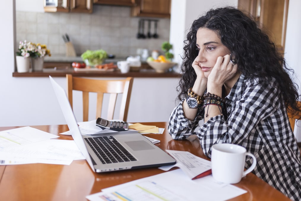 woman looking stressed while reviewing her finances after falling victim to a sweetheart scam