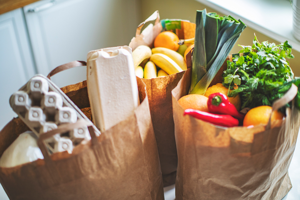 15 Easy Ways to Save Money on Groceries_three bags of groceries on kitchen table