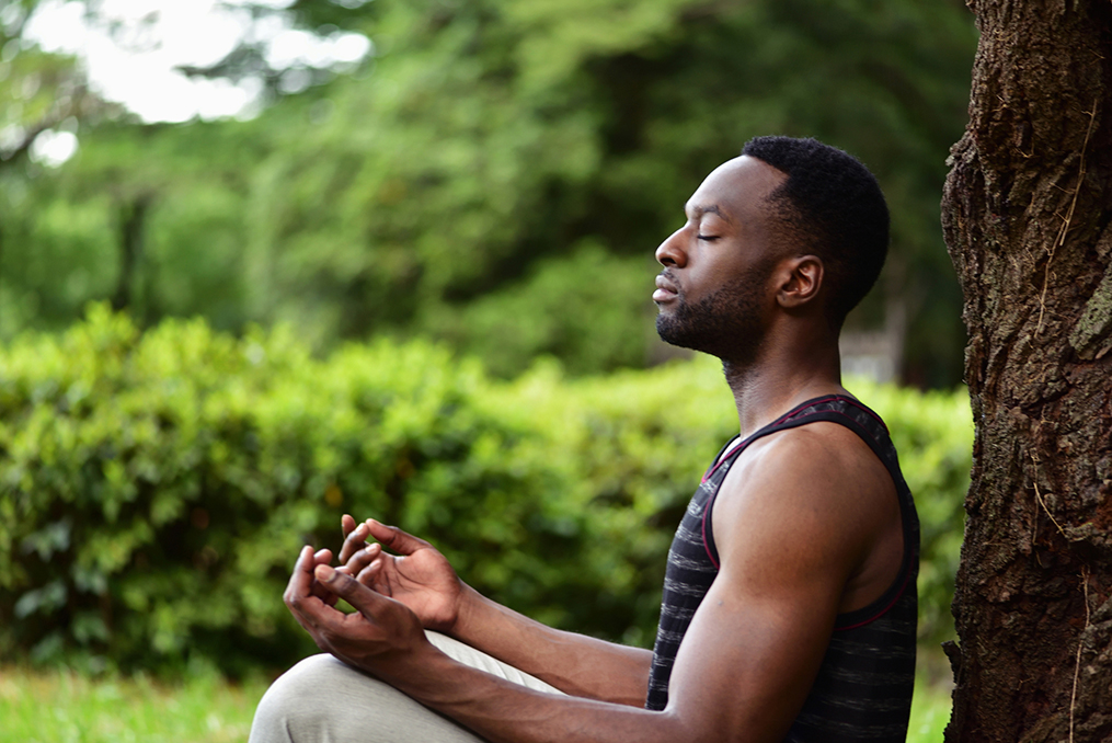 Commit to Getting Financially Fit in 2020_main in yoga pose meditating next to tree