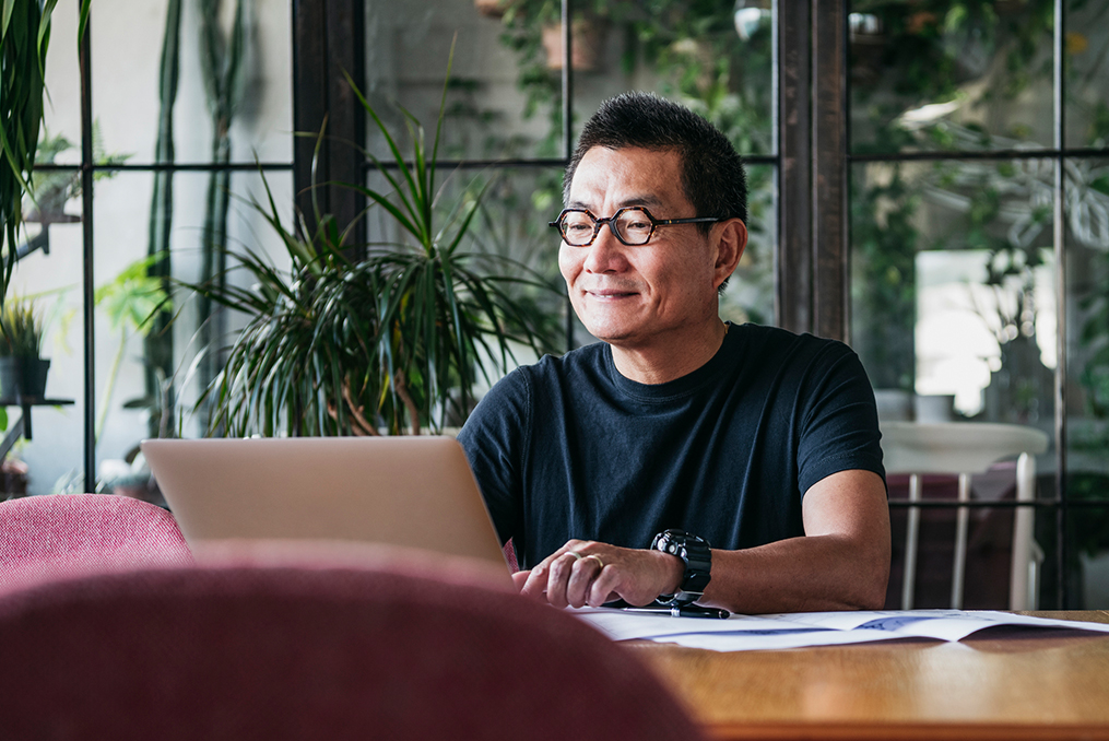 Commit to Getting Financially Fit in 2020_mature asian man sitting at a table reviewing his retirement plan with laptop