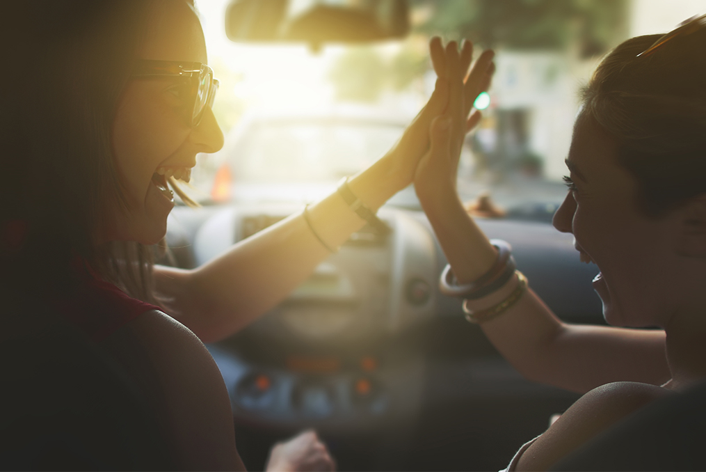 How to Buy Your Next Car with Confidence_Two women sitting in their car laughing and giving high fives