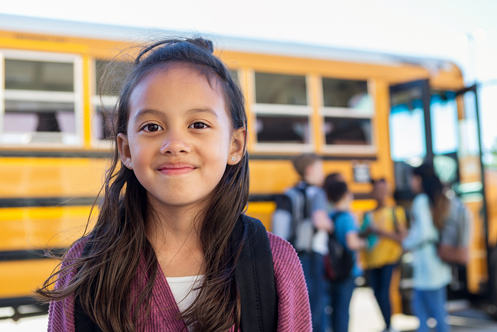 How to Get the Most From Your 529 Plan_young girl smiling standing next to the school bus with other children in the background
