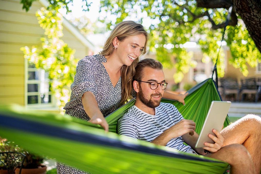 Take the time to organize your finances_Young man and woman sitting in a hammock reviewing personal finances
