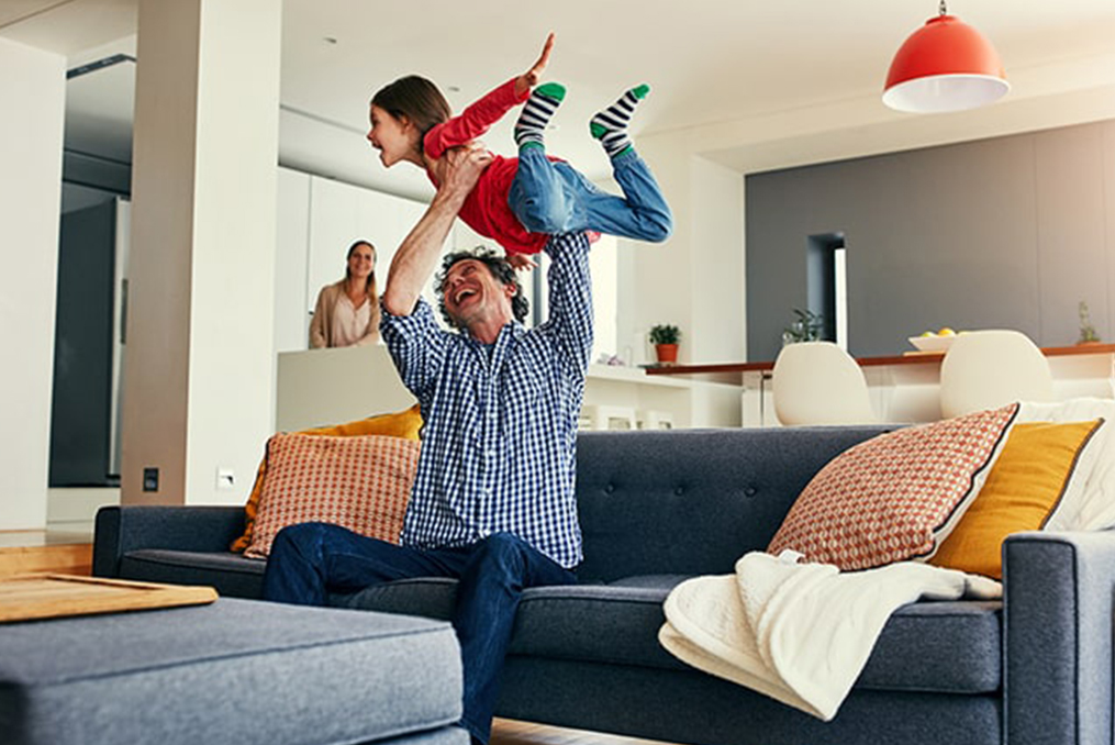 father holding his child in their living room