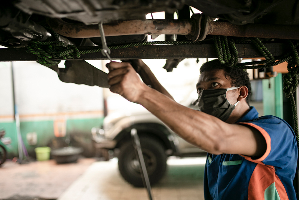 how to safely buy a used car_Mechanic inspecting vehicle on a lift