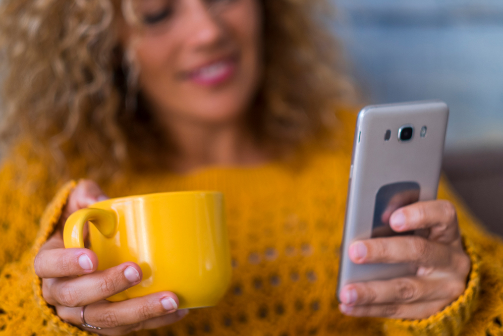 Save for Retirement When You Have Debt_woman using her phone while drinking a cup of coffee