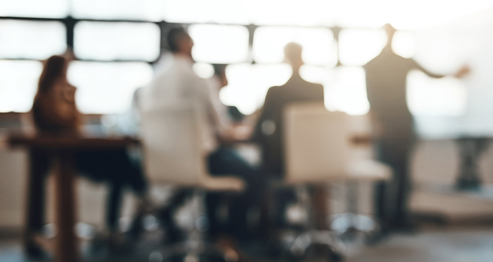 out of focus view of a meeting in a board room