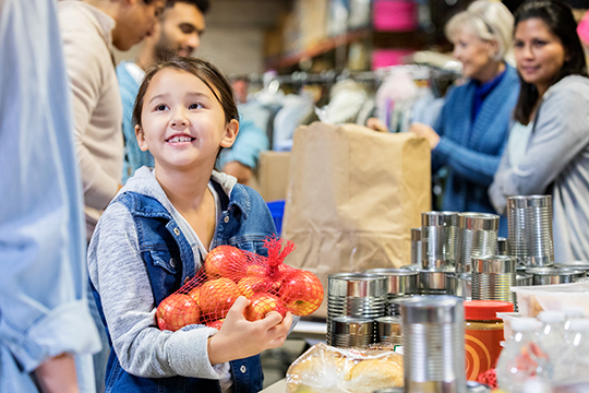 Young girl helps at food bank holding bag of oranges
