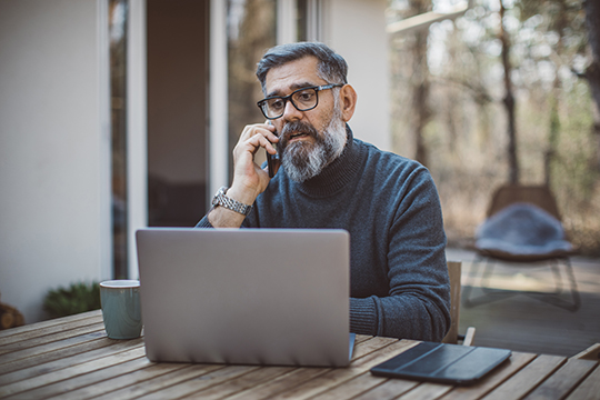 mature man on cell phone at laptop on patio and looking concerned
