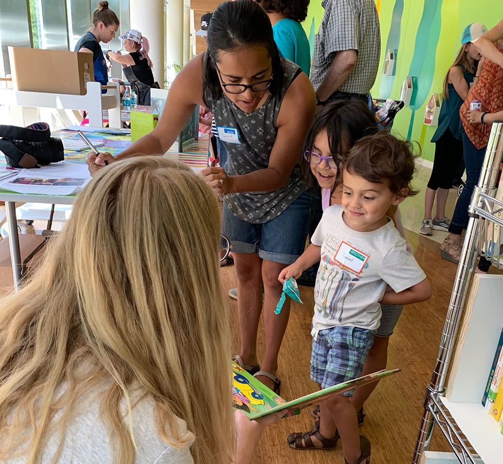 Volunteers of Babies with Books share books with young toddlers