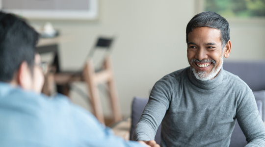 Confident mature Asian man sitting, smiling and shaking hand