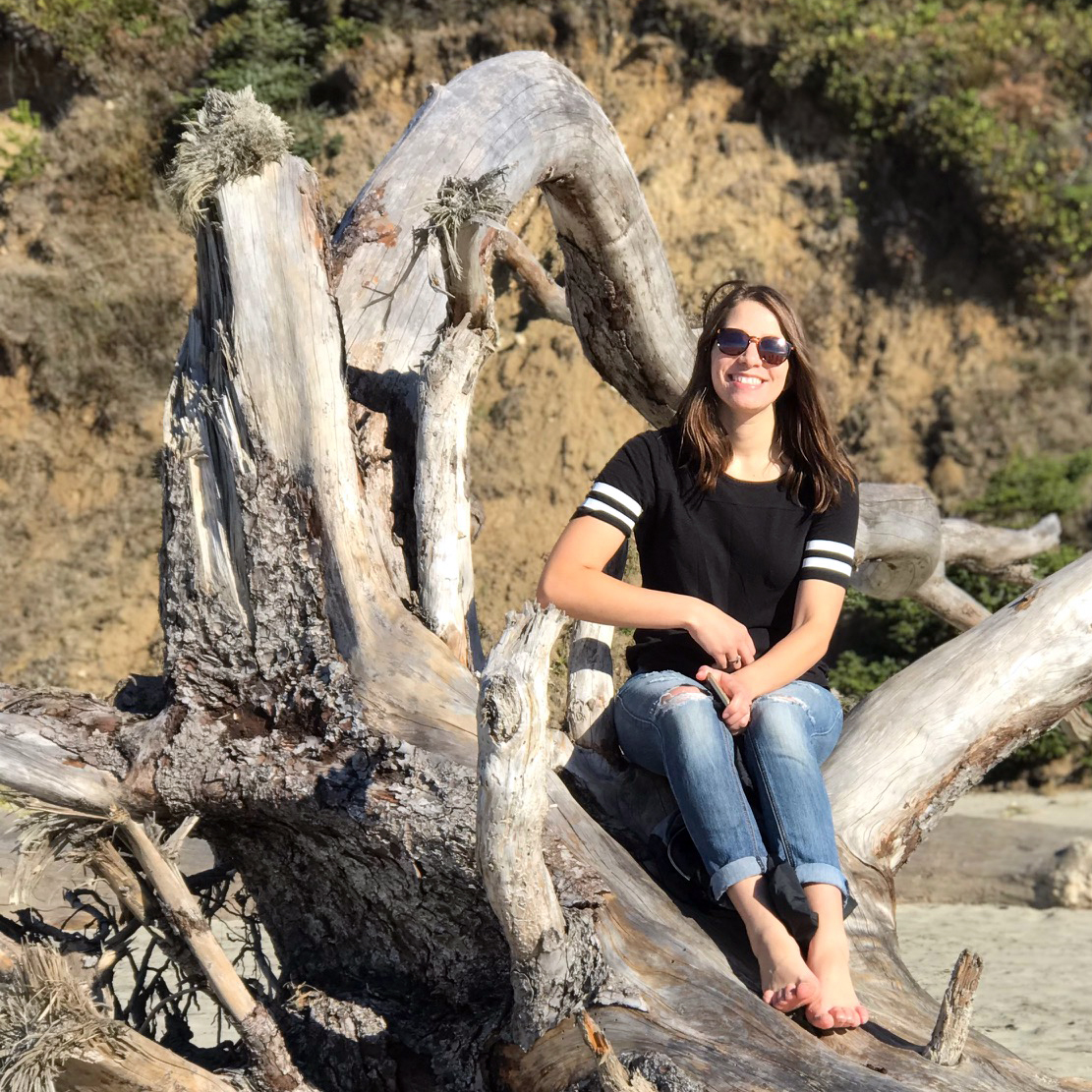 Abbygale sitting on driftwood at the beach