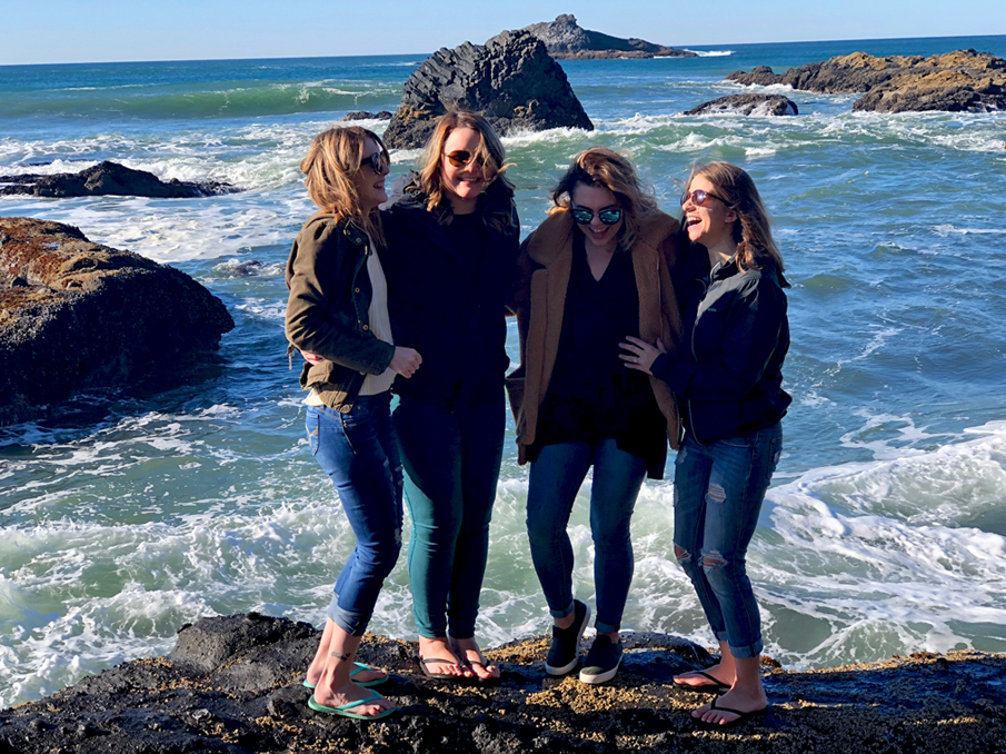 Abbygale standing with a group of friends near the ocean