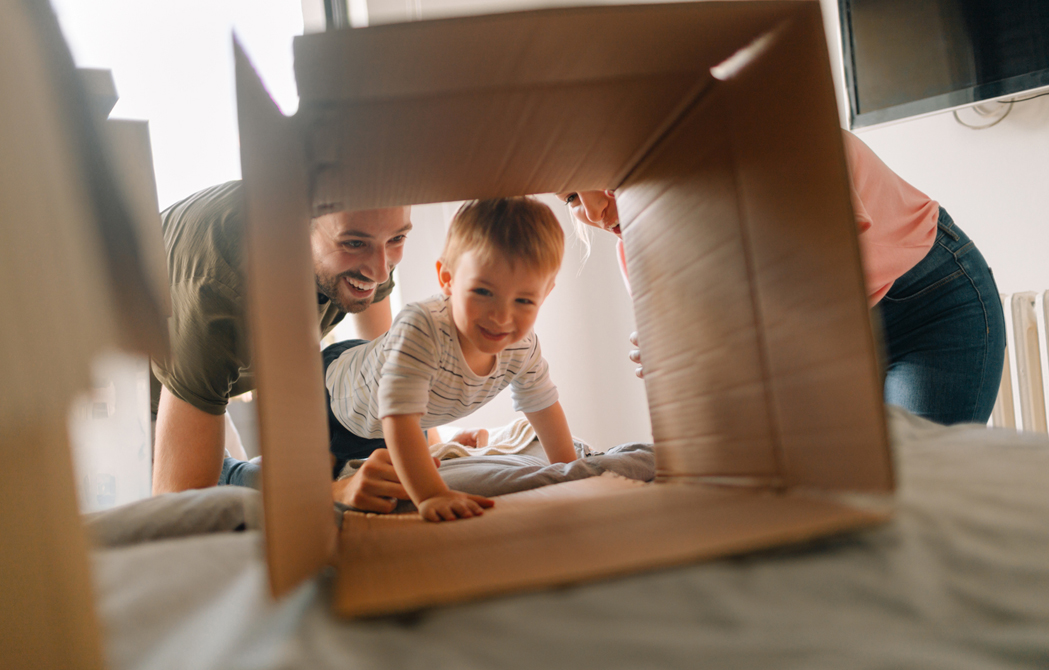 young couple watching their son crawl through a moving box on their bed