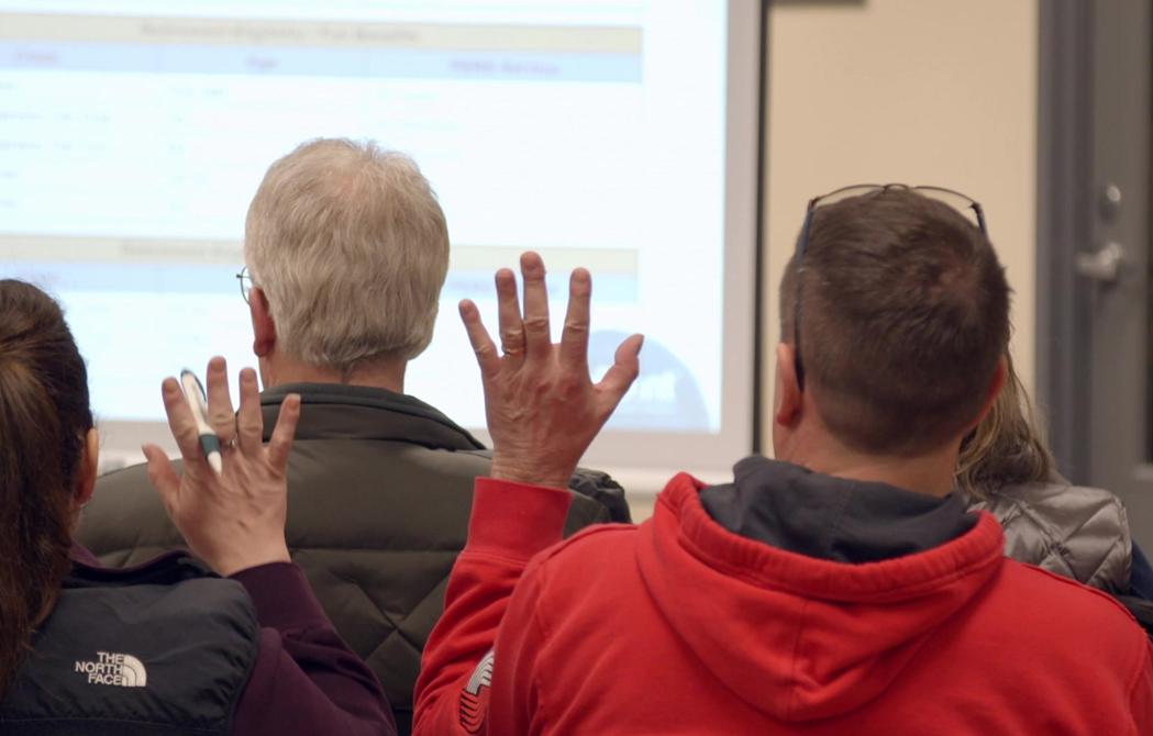 two seminar attendees raising their hands