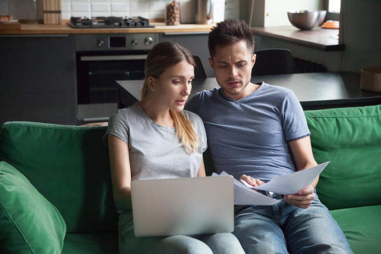 Worried couple calculating high domestic bills on laptop