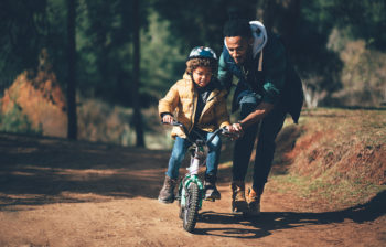 Young father teaching son how to ride bicycle in park