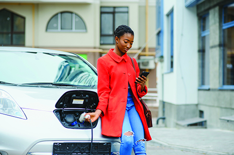 Young woman in bright red coat charging electric car at the charging station.