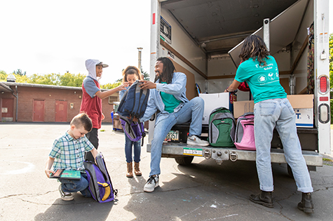 Man volunteering hands out backpacks and school supplies to young children.