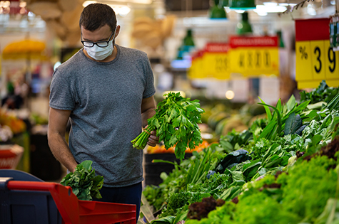 male wears mask against coronavirus while grocery shopping