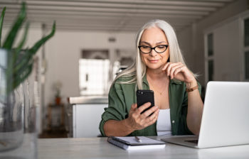 Woman at desk with laptop, looking at phone and finances.