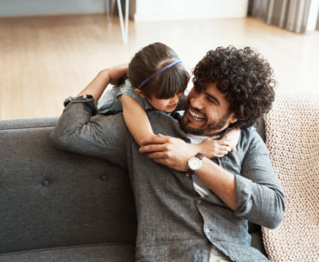 young daughter giving her father a hug on their couch