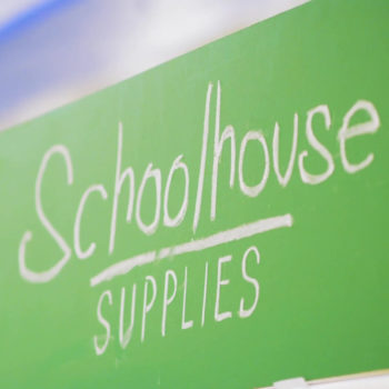 Photo of schoolhouse supplies written in chalk on a green chalk board