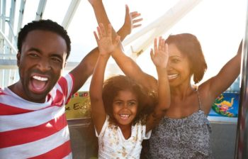 Parents with daughter raising arms and smilling on ferris wheel ride