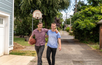Father and son walking into their home after playing basketball together