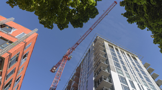 skyward view of two building construction projects and crane