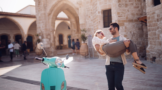 couple traveling in europe standing near a moped