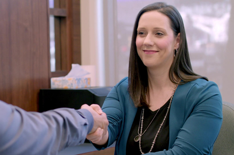 financial advisor natalie berning shaking hands with man across her desk